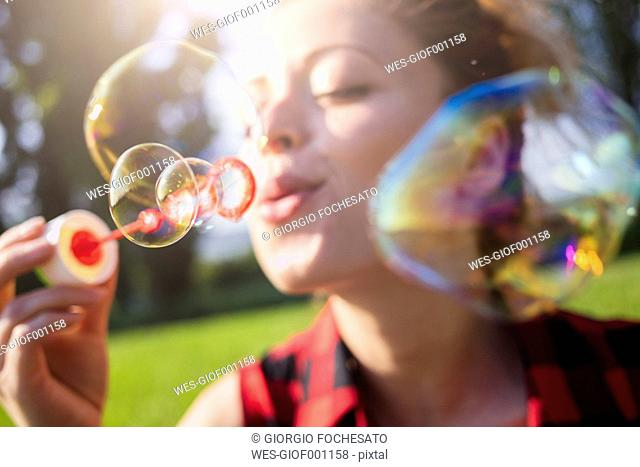 Woman blowing soap bubbles, close-up