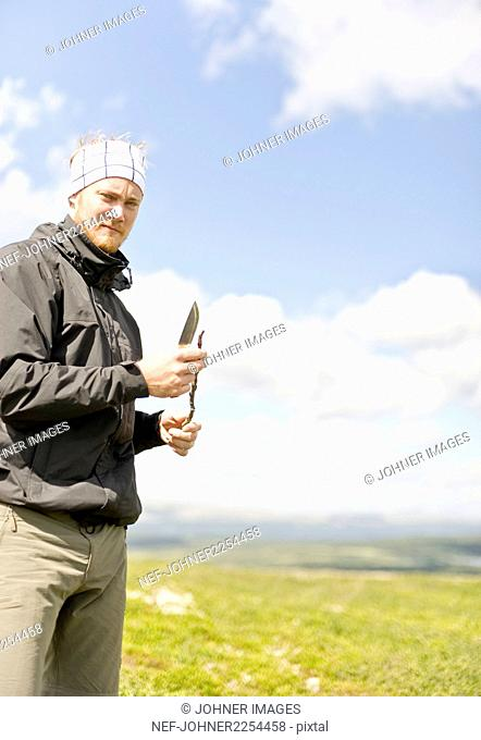 Hiker cutting twig with knife