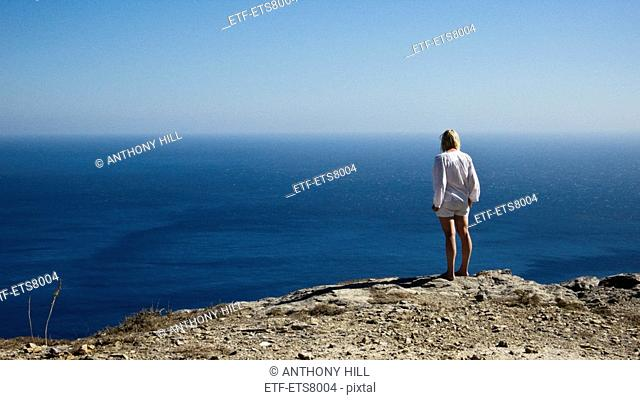 Woman watching the ocean Amorgos Greece