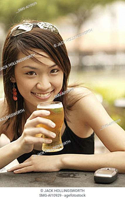 Young woman with a glass of beer, looking at camera
