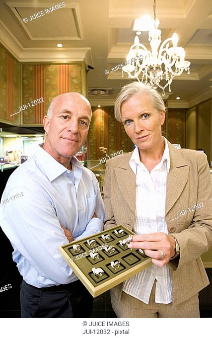 Mature jewellery shop assistants with tray of rings, smiling, portrait