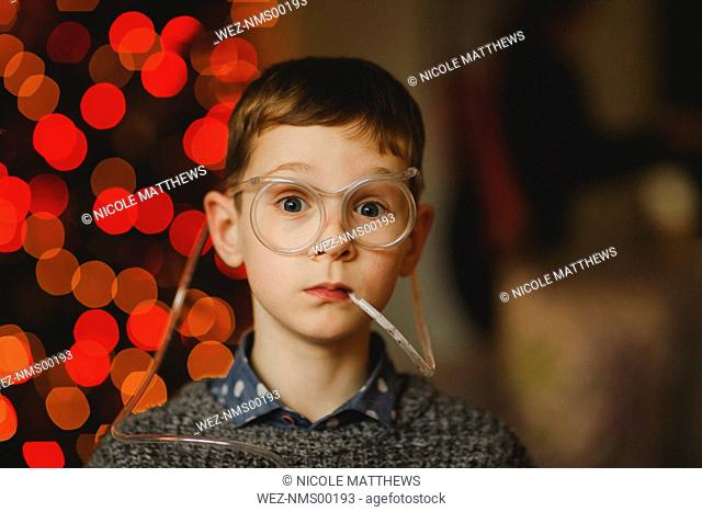 Portrait of boy wearing funny glasses with drinking straw