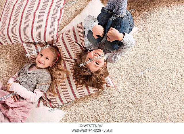 Germany, Cologne, Boy and girl 6-7 lying on carpet, elevated view
