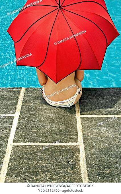 young woman sitting at poolside in shadow of big red umbrella