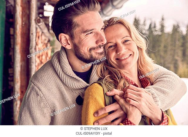 Portrait of romantic couple standing outside log cabin in winter, Elmau, Bavaria, Germany
