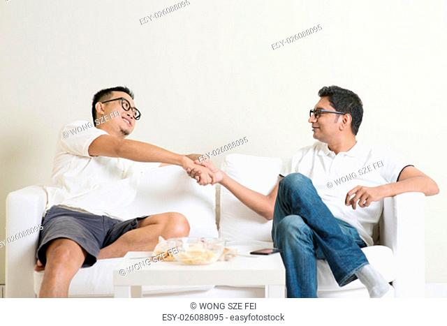 Man sitting on sofa and handshaking with friend at home. Multiracial people friendship