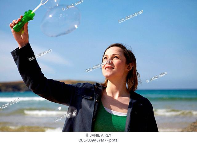 Young woman at coast with bubble wand