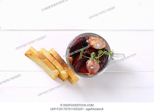 cup of baked beetroot and garlic with toasted bread on white wooden background
