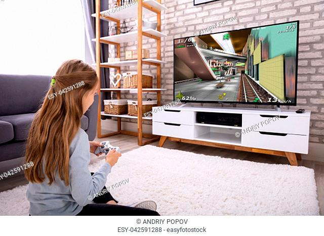 Girl Sitting On Carpet Playing Video Game On Television At Home