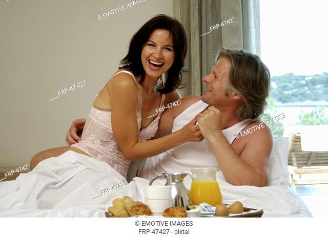 Couple is having breakfast in bed