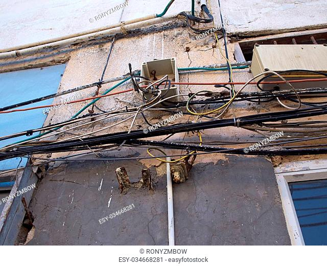 Tangled electric cable mess on a wall of building