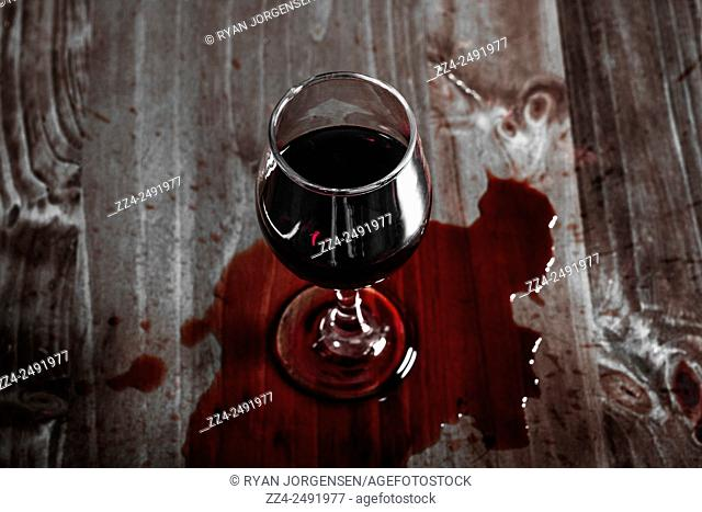 Artistic fine art still life photograph of an upright wineglass in a puddle or spill of red wine on a dining table. Dinner fallout concept