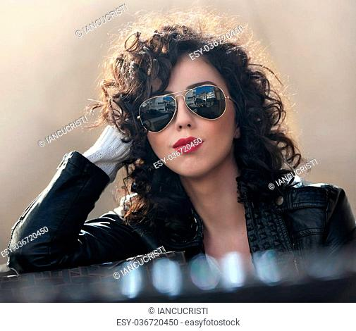 Charming young curly brunette woman with sunglasses and black leather jacket against wall. Sexy gorgeous young woman with modern look