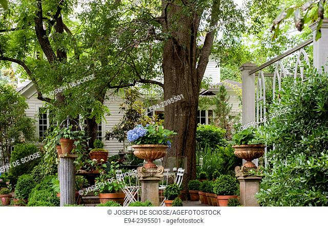 Outdoor living space in a garden setting featuring ferns and potted plants.Georgia USA