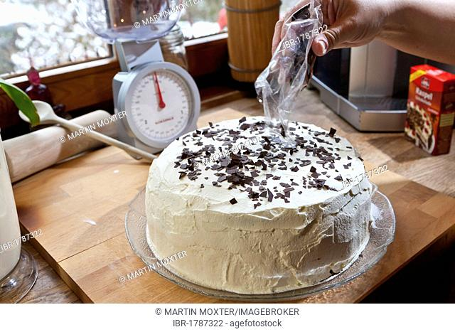 Preparation of a home-made Black Forest gateau, sprinkling chocolate flakes onto the cake