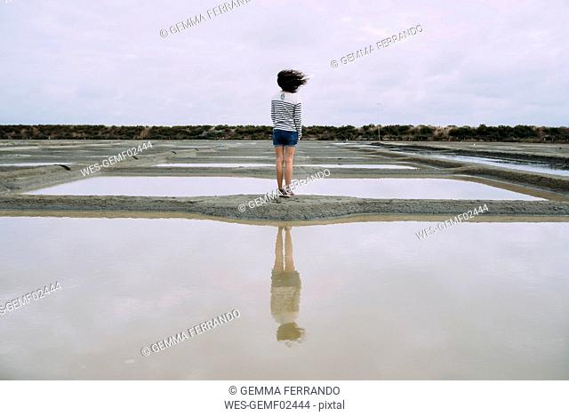 France, Bretagne, Woman surrounded by salt ponds in Marais salants de Guerande