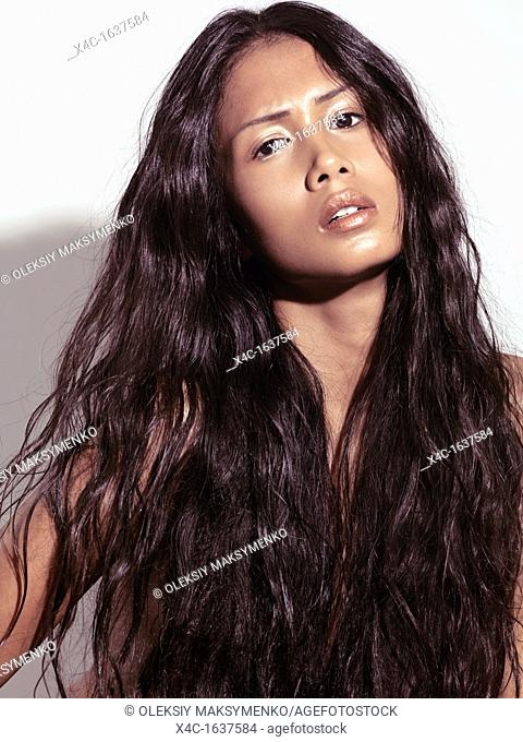 Expressive sensual beauty portrait of a young woman with long brown hair