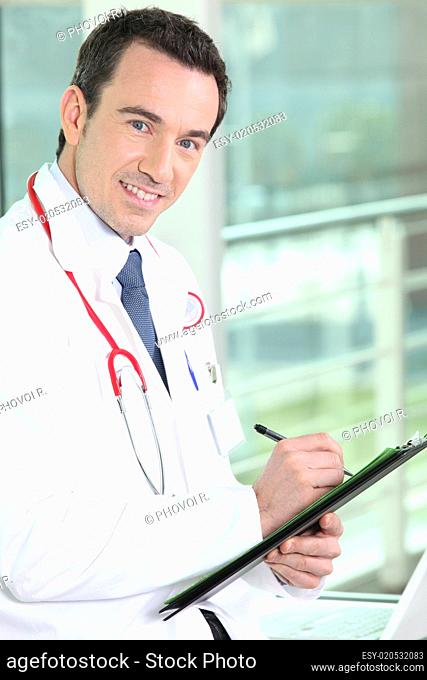 Smiling practitioner writing on medical record