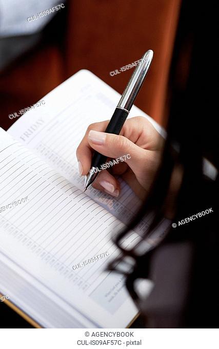 Close up of secretary making notes at meeting