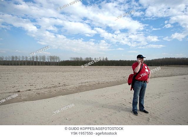 Almere, Netherlands. Lonely man having a conversation over his cell-phone, while standing in the sands of a suburb to be