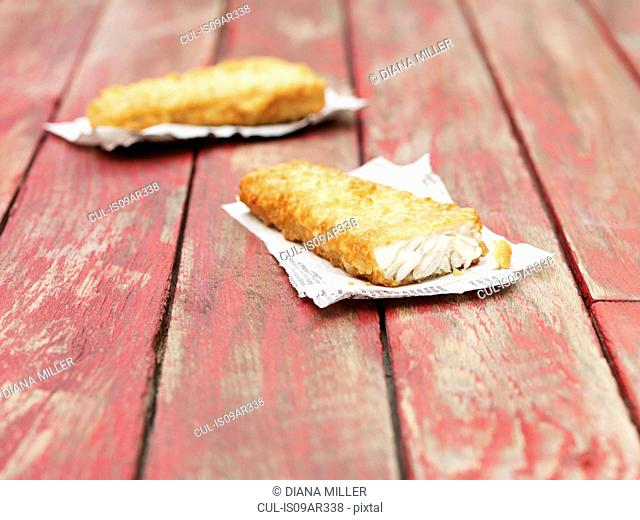 Two fried chunky battered cod pieces on red wooden table