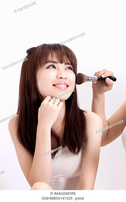 Young woman putting makeup by her friend happily
