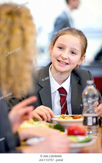 Smiling middle school student eating lunch and talking to friend in school cafeteria