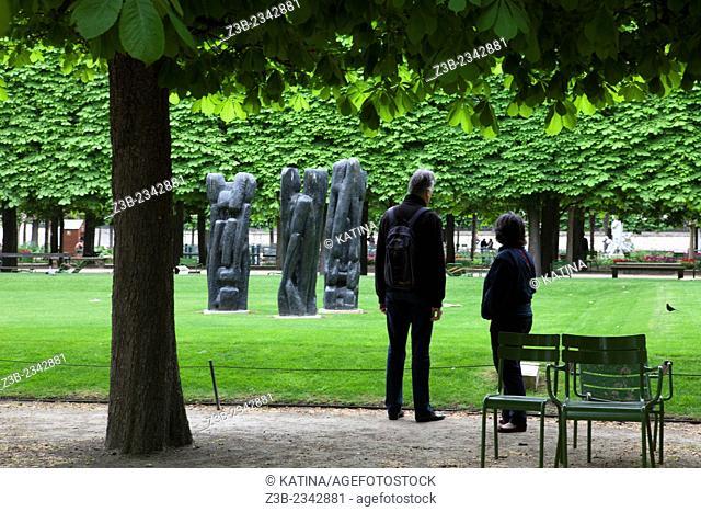 "Two people observe """"Personnage III"""" (1967) by Etienne Martin, Tuileries Gardens (Jardin des Tuileries) in spring, Paris, France, Europe"