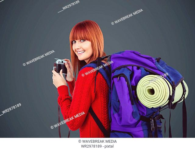 Millennial backpacker with camera against grey background