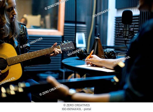 Two musicians in music studio, writing music