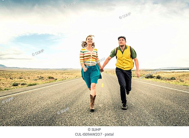 Retro style couple running hand in hand on road, Cody, Wyoming, USA