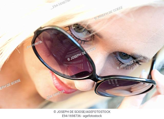 Portrait of a 29 year old blond woman outdoors, looking over sunglasses