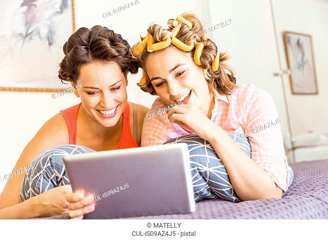 Two female friends, foam rollers in hair, lying on bed, using digital tablet