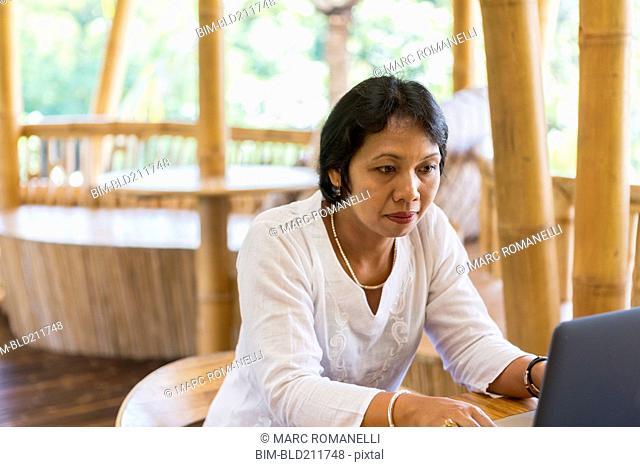 Balinese woman using laptop at table