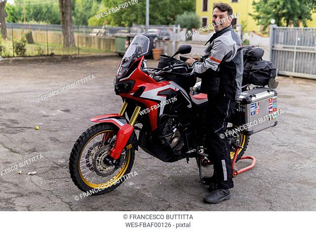 Portrait of smiling man preparing for a motorbike trip
