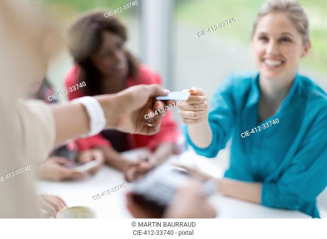 Smiling woman paying waitress with credit card reader at cafe table