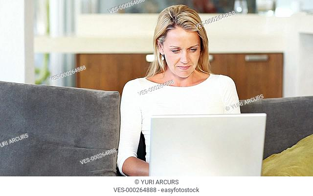 Pretty woman on her laptop at home, with her husband arriving to give her a hug and see what she's typing