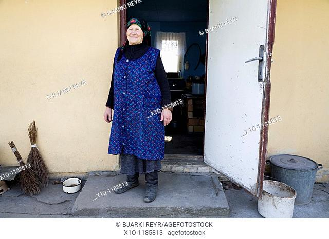 Old farmer outside her old house. She now lives in a newer farmhouse. Gmina Przylek, Zwolen county, Poland