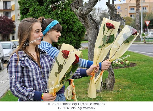 Two girls offering roses on the street at the feast of St  George, Dos chicas ofreciendo rosas en la calle en la fiesta de Sant Jordi