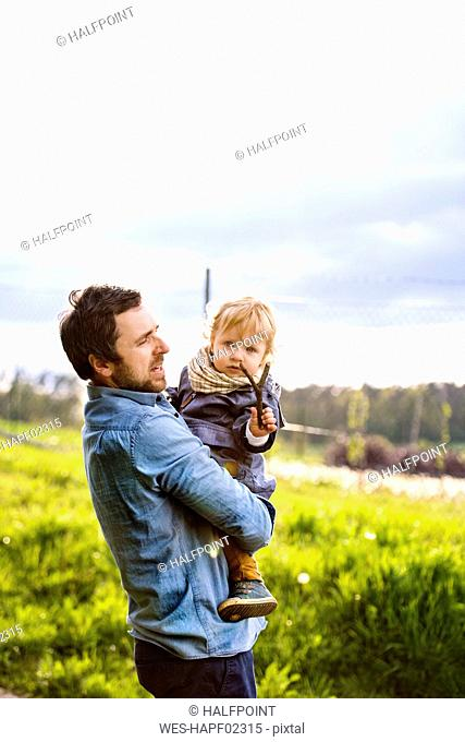 Father holding cute little boy with twig
