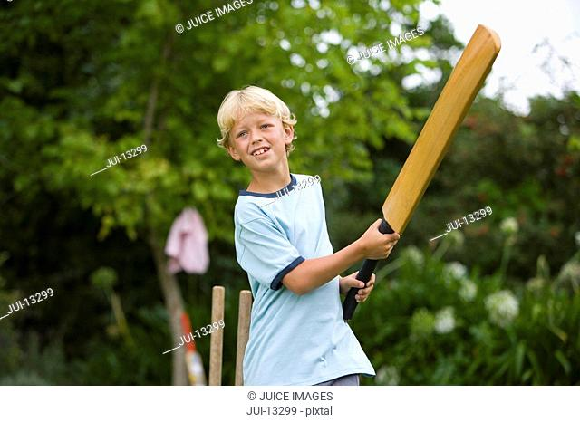 Boy 10-12 playing cricket, low angle view