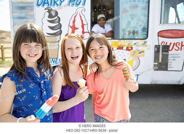 Portrait of cheerful little girls holding ice creams against van
