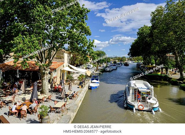 France, Aude, Saint Nazaire d'Aude, Canal du Midi listed as World Heritage by UNESCO, Port of Somail, boat of tourism passing in front of an open air dance hall...