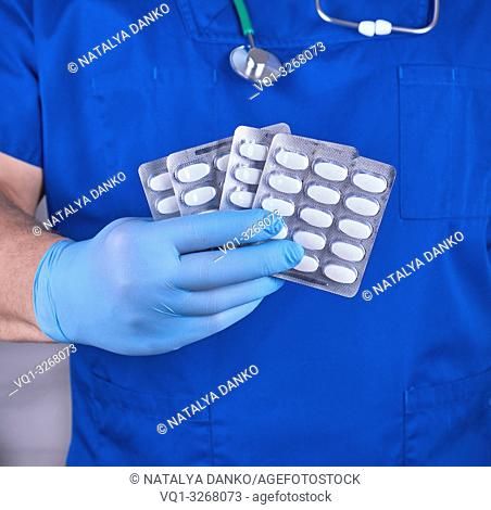 doctor in blue uniform and sterile gloves holding white pills in pack