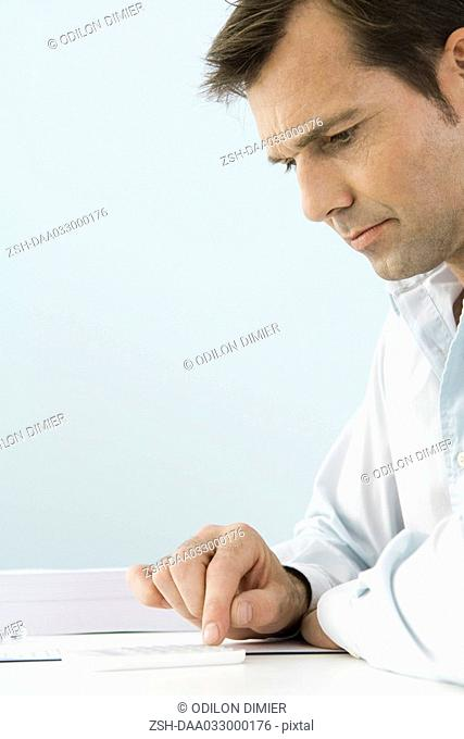 Man using calculator, sitting at table, side view