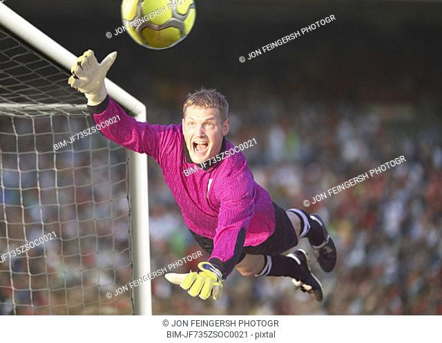 Male goalie reaching for the ball in midair