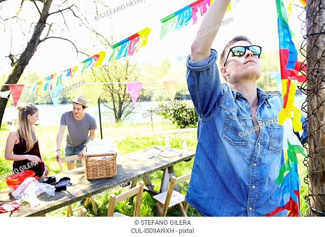 Young man hanging up bunting