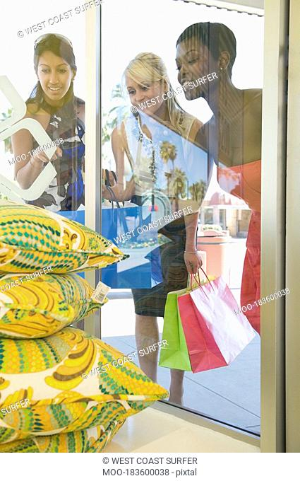 Female shoppers look at products through shop window