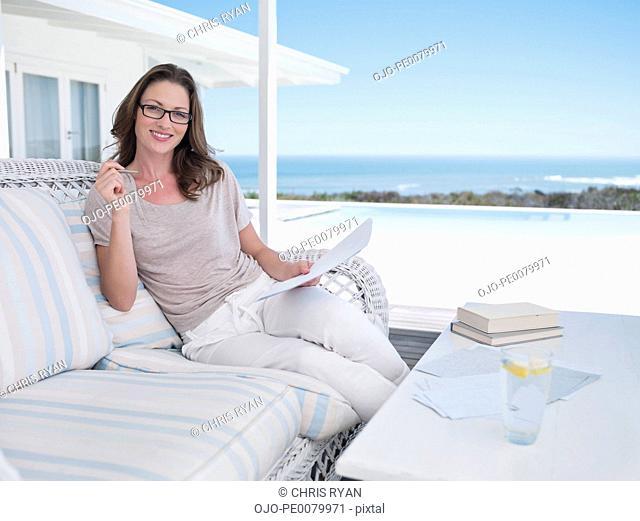 Portrait of smiling woman with paperwork on patio overlooking ocean