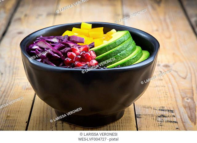 Lunch bowl with black rice, avocado, yellow bell pepper, red cabbage and pomegranate seed on wood